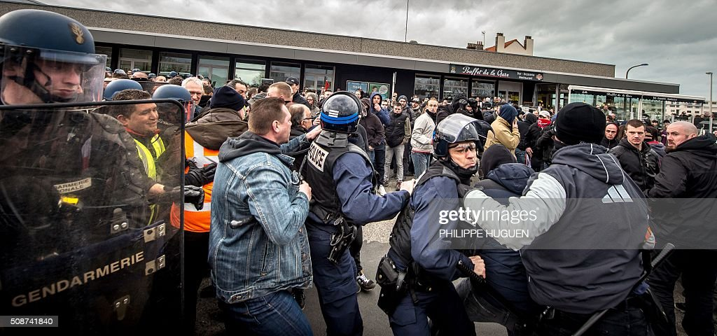 Policemen and anti-riots gendarmes arrest supporters of the Pegida movement (Patriotic Europeans Against the Islamisation of the Occident) during a demonstration in Calais, northern France on February 6, 2016. Anti-migrant protesters in the French port city of Calais clashed with police as they defied a ban and rallied in support of a Europe-wide initiative by the Islamophobic Pegida movement. / AFP / PHILIPPE HUGUEN