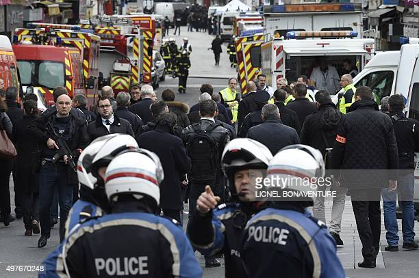 Policemen and firefighters are at work in a security perimeter set in the northern Paris suburb of SaintDenis city center on November 18 to secure...