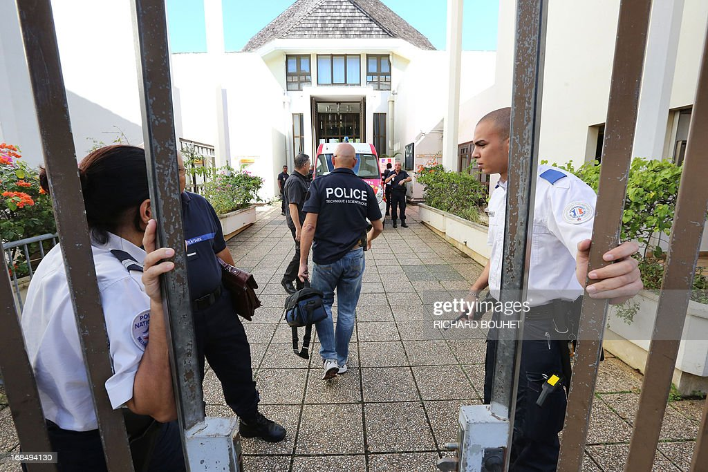 Policemen and firefighters stand at the entrance of the Champ-Fleuri courthouse in the Saint-Denis de la Reunion, on the French island of La Reunion, after a man set himself on fire on May 10, 2013. Desperate doused himself with gasoline and inflamed the liquid. He then ran into the Salle des Pas Perdus. Alerted the emergency services went to the scene. The courthouse was evacuated.