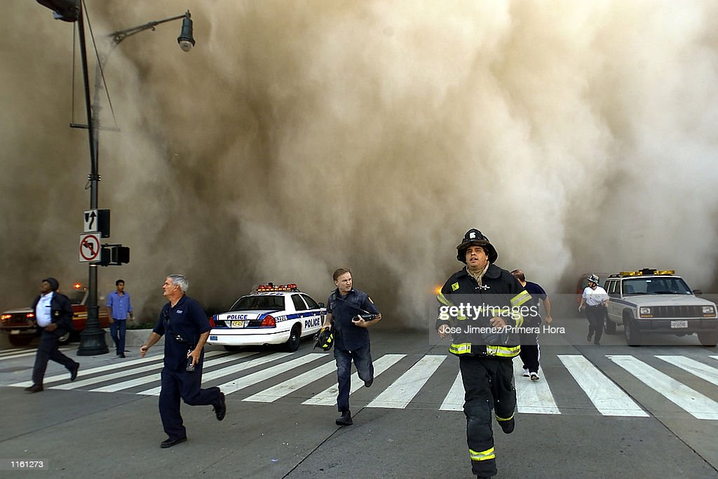 Policemen and firemen run away from the huge dust cloud caused as the World Trade Center's Tower One collapses after terrorists crashed two hijacked planes into the twin towers, September 11, 2001 in New York City.