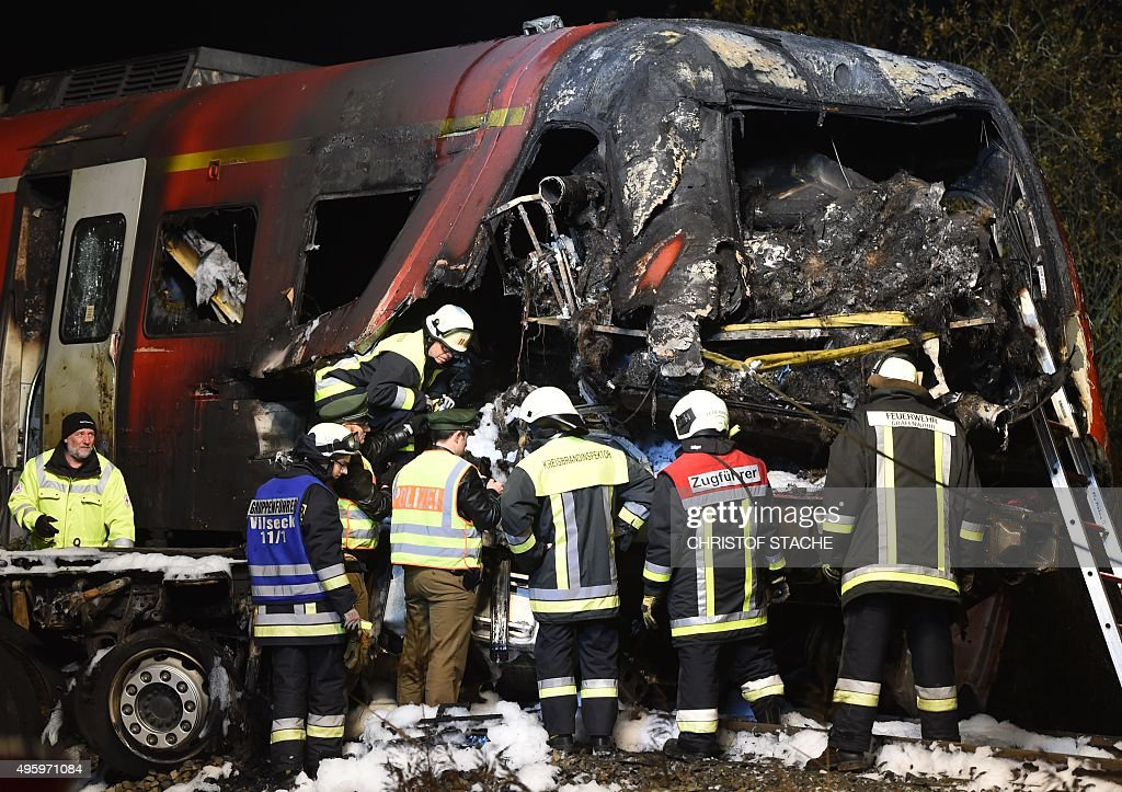 Policemen and fireworkers stand beside the destroyed cockpit of a regional train after it collided with a lorry at a crossing near the village...