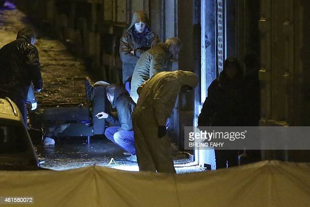 Policemen and forencic police work into a marked out perimeter in Colline street in Verviers eastern Belgium on January 15 after two men were...
