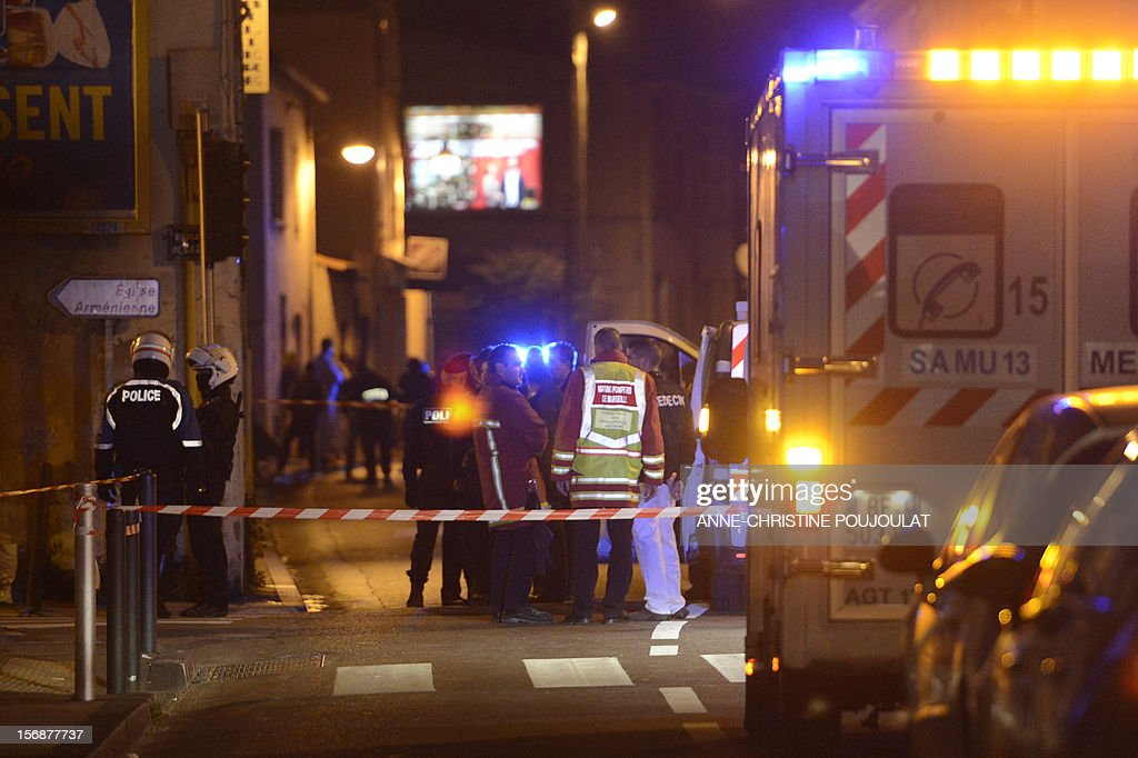 Policemen and forensics experts investigate at a crime scene on November 23, 2012, in Marseille, after a man was shot dead. The killing brings to 24 the number of people murdered during the settling of scores in the Marseille region since January, including 18 in the city.