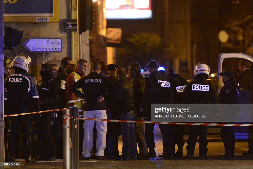 Policemen and forensics experts investigate at a crime scene on November 23, 2012, in Marseille, after a man was shot dead. The killing brings to 24 the number of people murdered during the settling of scores in the Marseille region since January, including 18 in the city. AFP PHOTO / ANNE-CHRISTINE POUJOULAT