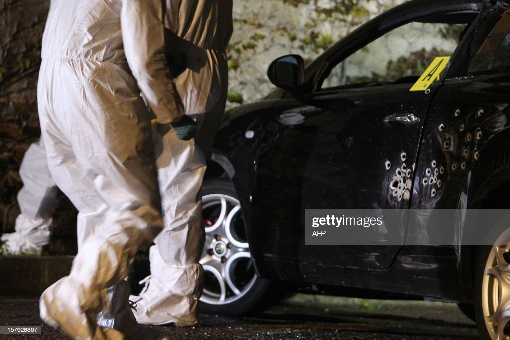 Policemen and forensics investigate on a crime scene on December 7, 2012, in Calvi, in the French Mediterranean island of Corsica. A 30 years old man was killed and his son, 11, was slightly injured.