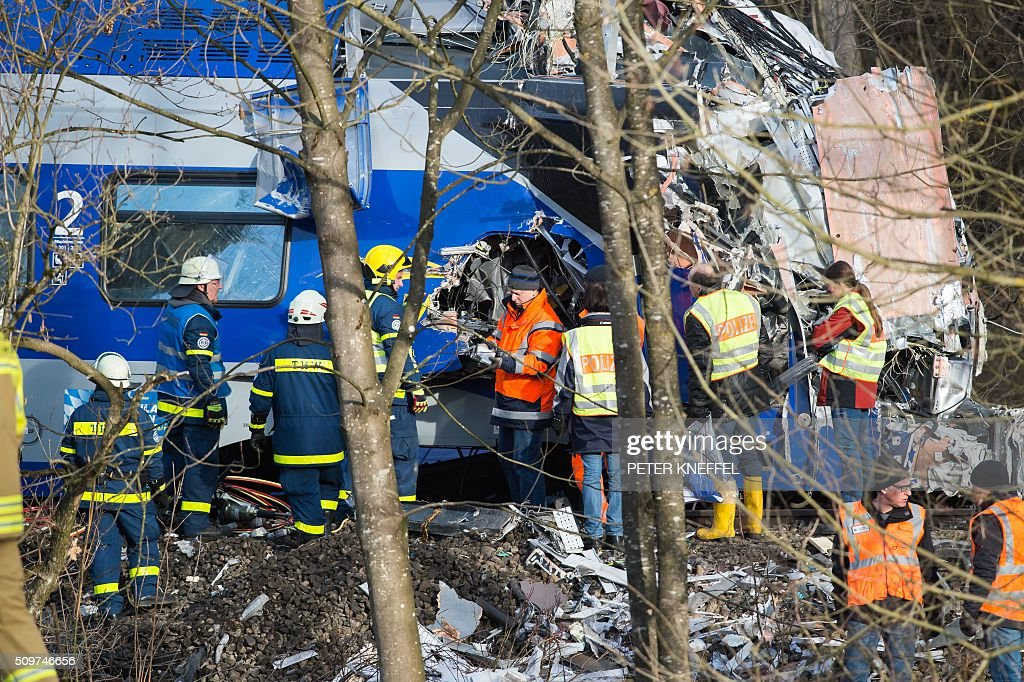 Policemen and helpers of the THW technical relief unit work at the site of a train accident near Bad Aibling, southern Germany, on February 12, 2016. German investigators try to determine what caused the train crash that killed 10 people, while media reports said that human error was to blame. / AFP / dpa / Peter Kneffel / Germany OUT