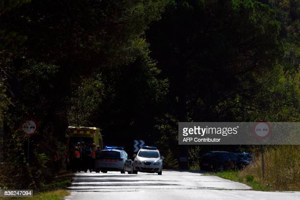 Policemen and medical staff stand next to their vehicles where Moroccan suspect Younes Abouyaaqoub was shot on August 21 2017 near Sant Sadurni...