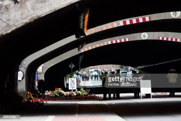 Policemen and rescue workers stand in front of flowers and candles laid down at the tunnel where 21 visitors of the Love Parade music festival died...