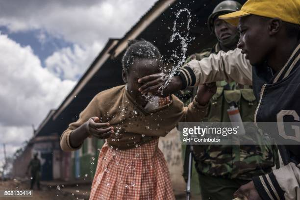 Policemen and residents help a young schoolgirl that inhaled tear gas as the police was trying to hold off a group of supporters of opposition leader...
