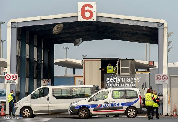 Policemen and security employees search a truck bound for Britain at the ferry terminal of the port of Calais on September 21 2016 / AFP / PHILIPPE...