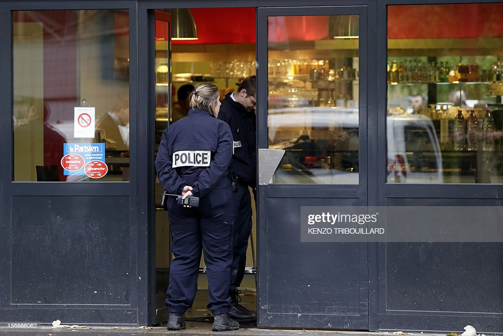 Policemen are at work in a bar where one people was shot dead and four others wounded by one or several shooters driving in a BMW, on November 23, 2012 in Orly-Ville, outside Paris.