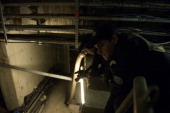 Policemen are pictured as they look for kits used by drug dealers during a patrol in the tunnels under the Gare du Nord in Paris on December 05 2012...