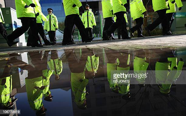 Policemen are reflected in a puddle as they march around the secure area surrounding the venue for the G20 Summit in Seoul on November 12 2010 South...