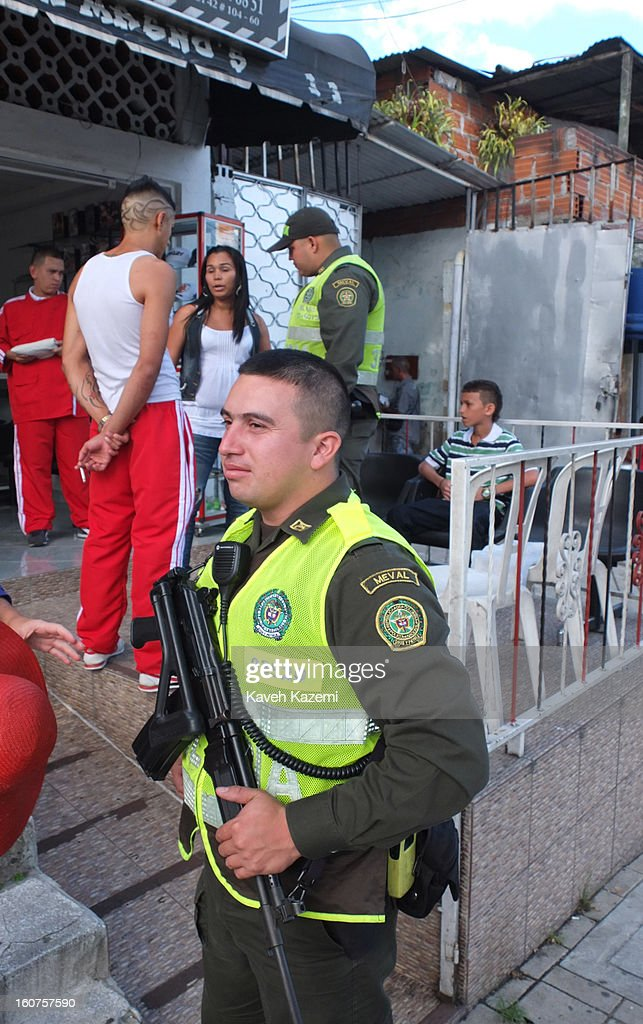 Policemen armed with automatic assault rifles make an enquiry outside a barber shop in the Comuna 13 slums on January 5, 2013 in Medellin, Colombia. Comuna 13 is the most notorious slums of Medellin with violence occurring everyday.