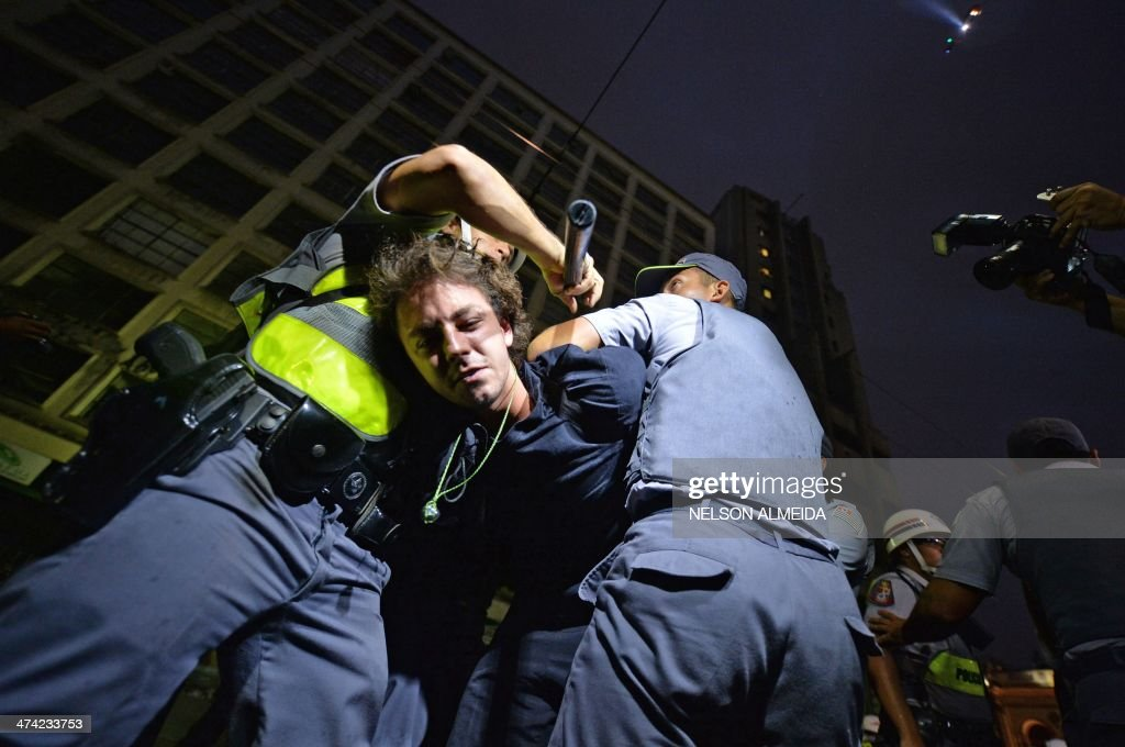 Policemen arrest a demonstrator during a protest against the government's expenditure for the 2014 FIFA World Cup in Sao Paulo, Brazil on February 22, 2014. AFP PHOTO / NELSON ALMEIDA