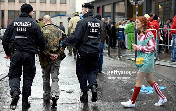Policemen arrest a man during Weiberfastnacht celebrations as part of the carnival season on February 4 2016 in Cologne Germany Carnival partying and...