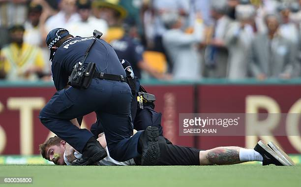 Policemen arrest a spectator after he ran onto the field during the second day of the daynight cricket Test match between Australia and Pakistan at...