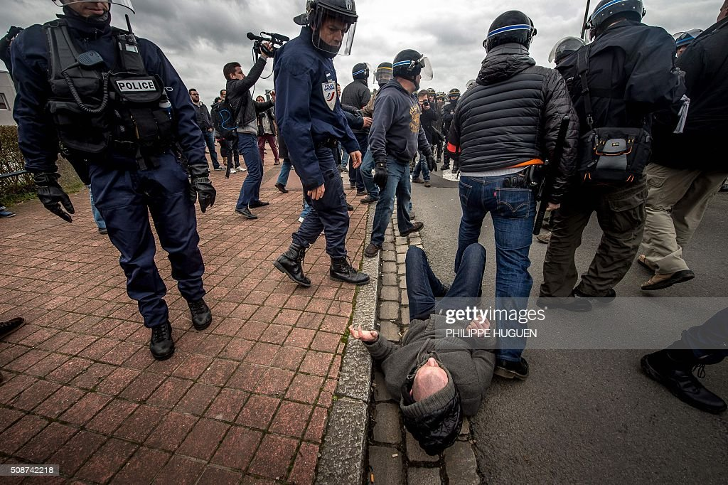 Policemen arrest a supporte of the Pegida movement (Patriotic Europeans Against the Islamisation of the Occident) during a demonstration in Calais, northern France on February 6, 2016. Anti-migrant protesters in the French port city of Calais clashed with police as they defied a ban and rallied in support of a Europe-wide initiative by the Islamophobic Pegida movement. / AFP / PHILIPPE HUGUEN