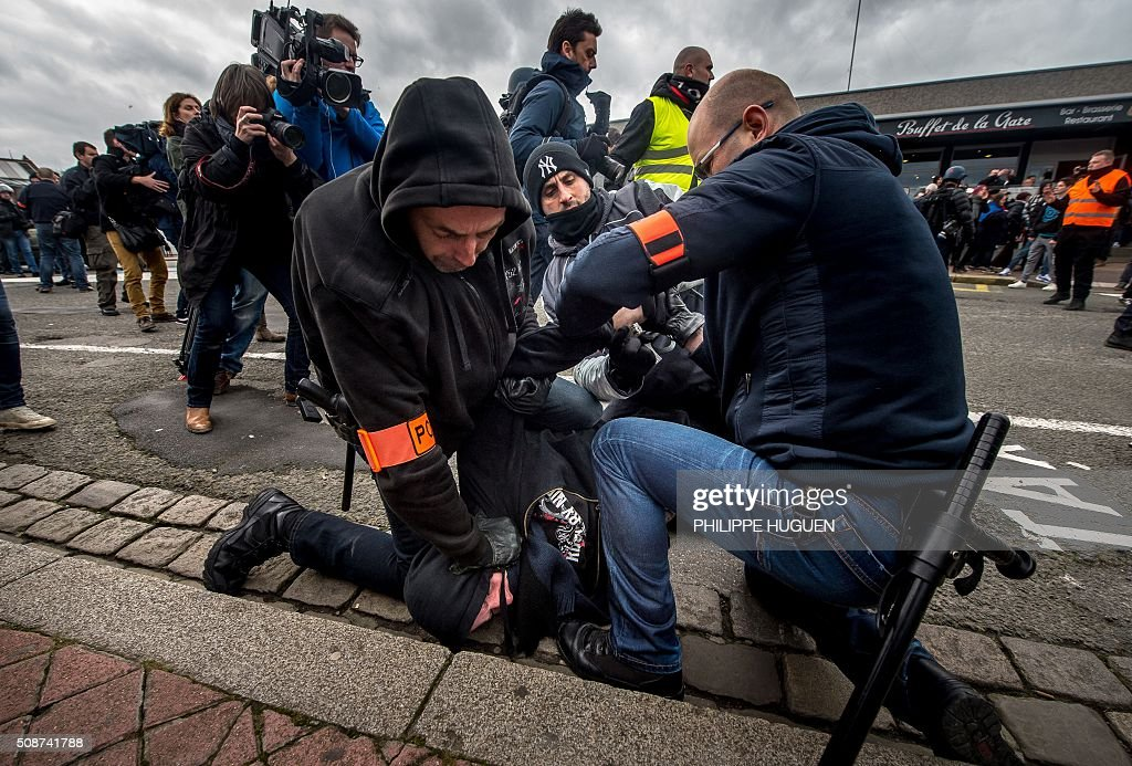 Policemen arrest a supporter of the Pegida movement (Patriotic Europeans Against the Islamisation of the Occident) during a demonstration in Calais, northern France on February 6, 2016. Anti-migrant protesters in the French port city of Calais clashed with police as they defied a ban and rallied in support of a Europe-wide initiative by the Islamophobic Pegida movement. / AFP / PHILIPPE HUGUEN