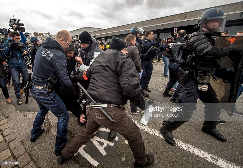 Policemen arrest supporters of the Pegida movement (Patriotic Europeans Against the Islamisation of the Occident) during a demonstration in Calais, northern France on February 6, 2016. Anti-migrant protesters in the French port city of Calais clashed with police as they defied a ban and rallied in support of a Europe-wide initiative by the Islamophobic Pegida movement. / AFP / PHILIPPE HUGUEN