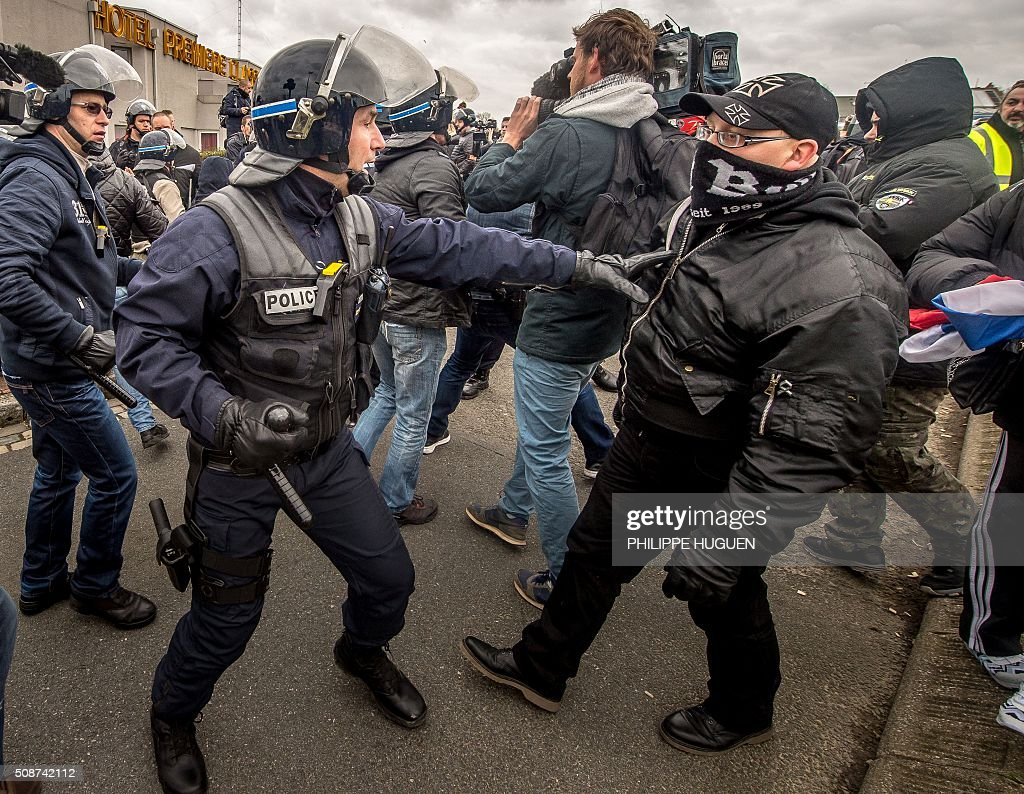 Policemen arrest supporters of the Pegida movement (Patriotic Europeans Against the Islamisation of the Occident) confronts policemen during a demonstration in Calais, northern France on February 6, 2016. Anti-migrant protesters in the French port city of Calais clashed with police as they defied a ban and rallied in support of a Europe-wide initiative by the Islamophobic Pegida movement. / AFP / PHILIPPE HUGUEN