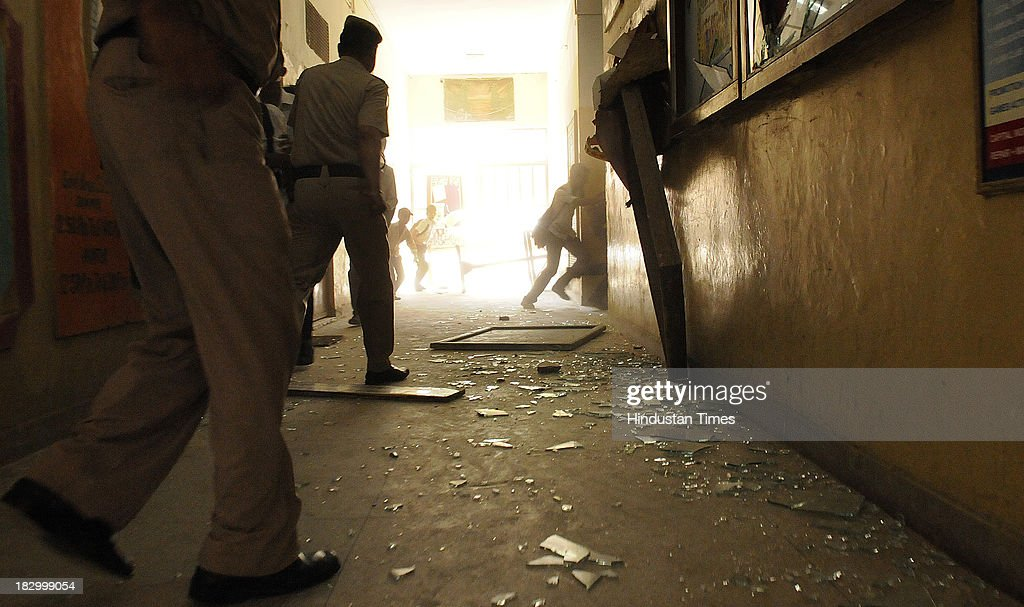Policemen arrive at Government Boys Senior School, Chittaranjan Park after students protest against the Principal over injury of class 4th student Roshan Lama on October 3, 2013 in New Delhi, India. 11 year old boy Roshan Lama is battling for life at AIIMS Trauma Centre after a javelin, thrown by a senior student during a practice session, pierced his skull at a school playground in CR Park area of south Delhi two days ago.
