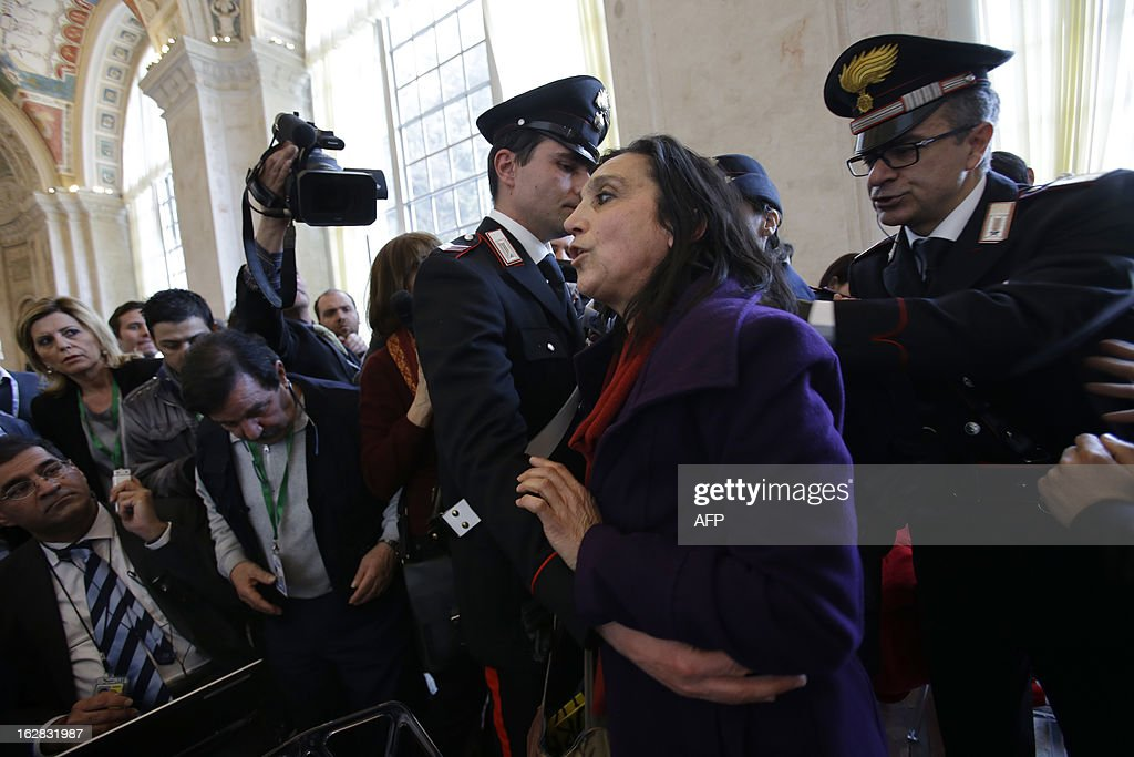 Policemen block a peace activist who would not give her name after she protested what she said is the killing of innocent civilians by countries including the U.S. and Italy, at the end of statements given by U.S. Secretary of State John Kerry, Syrian National Coalition President Mouaz al-Khatib, and Italian Foreign Minister Giulio Terzi (not pictured) during a joint press conference at the end of a meeting of the 'Friends of the Syrian People (FOSP) Ministerial' group on February 28, 2013 in Rome.