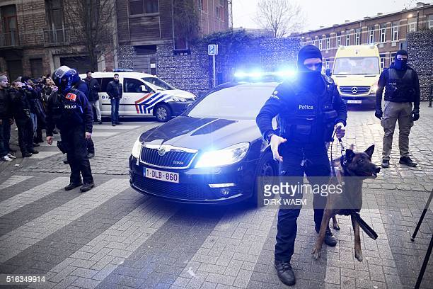 Policemen block a road near the scene of a police raid in the MolenbeekSaintJean district in Brussels on March 18 as part of the investigation into...