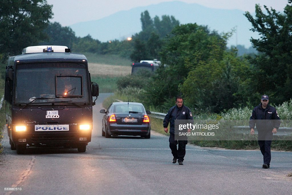 Policemen block the road to the migrant camp during an evacuation operation of the makeshift camp at the Greek-Makedonian border near the village of Idomeni on May 24, 2016. In an operation which began shortly after sunrise on May 24, hundreds of Greek police began evacuating the sprawling camp which is currently home to 8,400 refugees and migrants, among them many families with children, an AFP correspondent said. At its height, there were more than 12,000 people crammed into the site, many of them fleeing war, persecution and poverty in the Middle East and Asia, with the camp exploding in size since Balkan states began closing their borders in mid February in a bid to stem the human tide seeking passage to northern Europe. / AFP / SAKIS