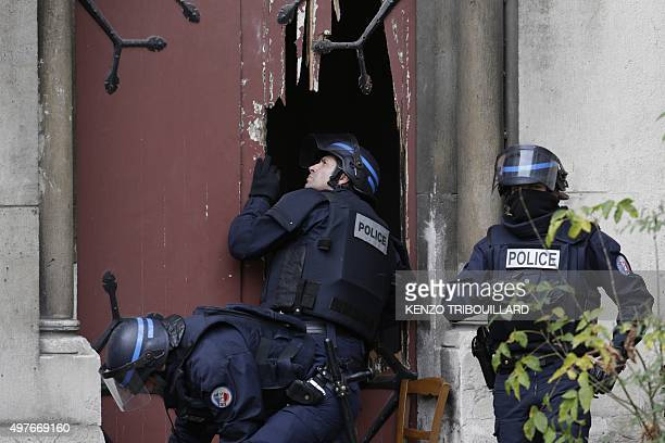 Policemen break a door to enter a church in the northern Paris suburb of SaintDenis city center on November 18 to secure the area after French Police...