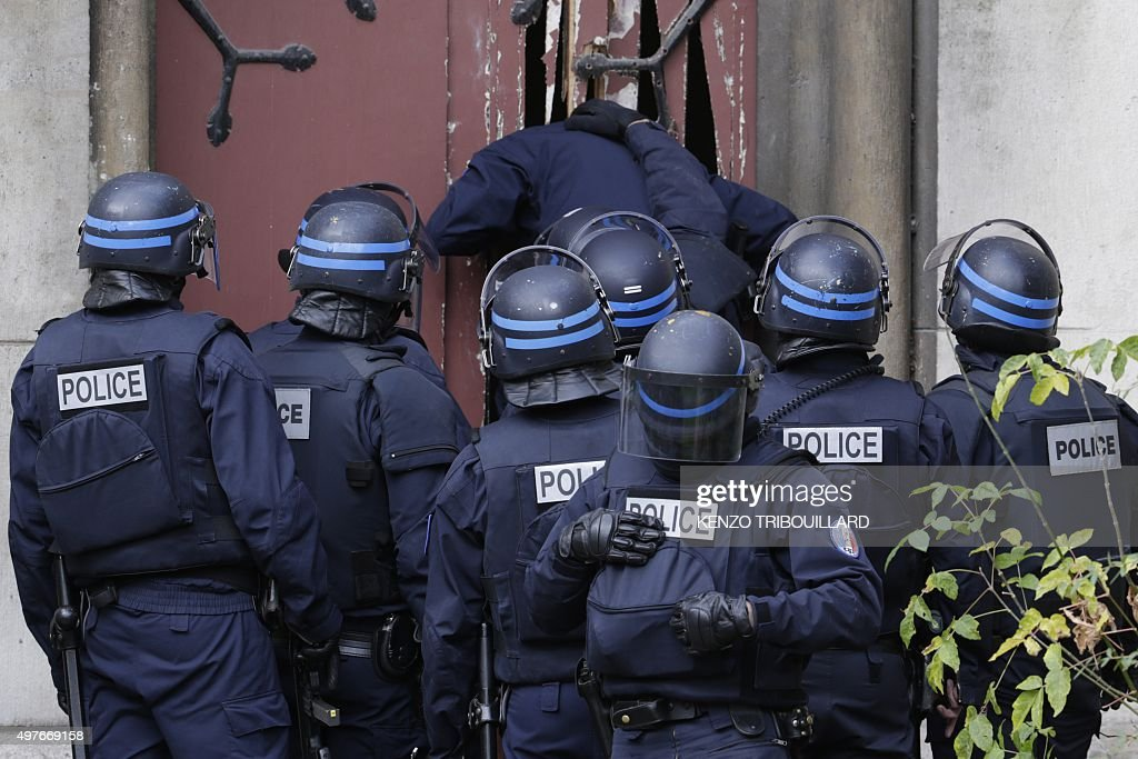 Policemen breaks a door to enter a church in the northern Paris suburb of SaintDenis city center on November 18 to secure the area after French...