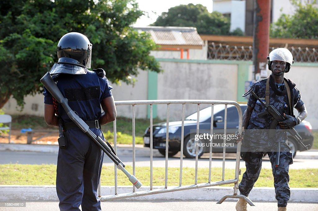 Policemen carry a barrier as they try to stop supporters of the opposition New Patriotic Party from marching to the Electoral Commission's...