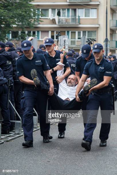 Policemen carry a protester away from a demonstration in front of the Sejm building in Warsaw Poland on 20 July 2017 People protest against...
