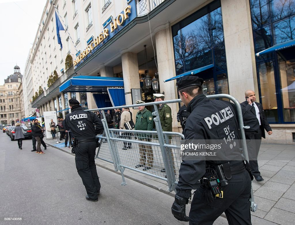 Policemen carry crowd barriers as security measures are executed in front of the Bayerischer Hof hotel, venue of the 52nd Munich Security Conference (MSC), prior to the start of the conference in Munich, southern Germany, on February 12, 2016. The Munich Security Conference takes place here until February 14, 2016. / AFP / THOMAS KIENZLE
