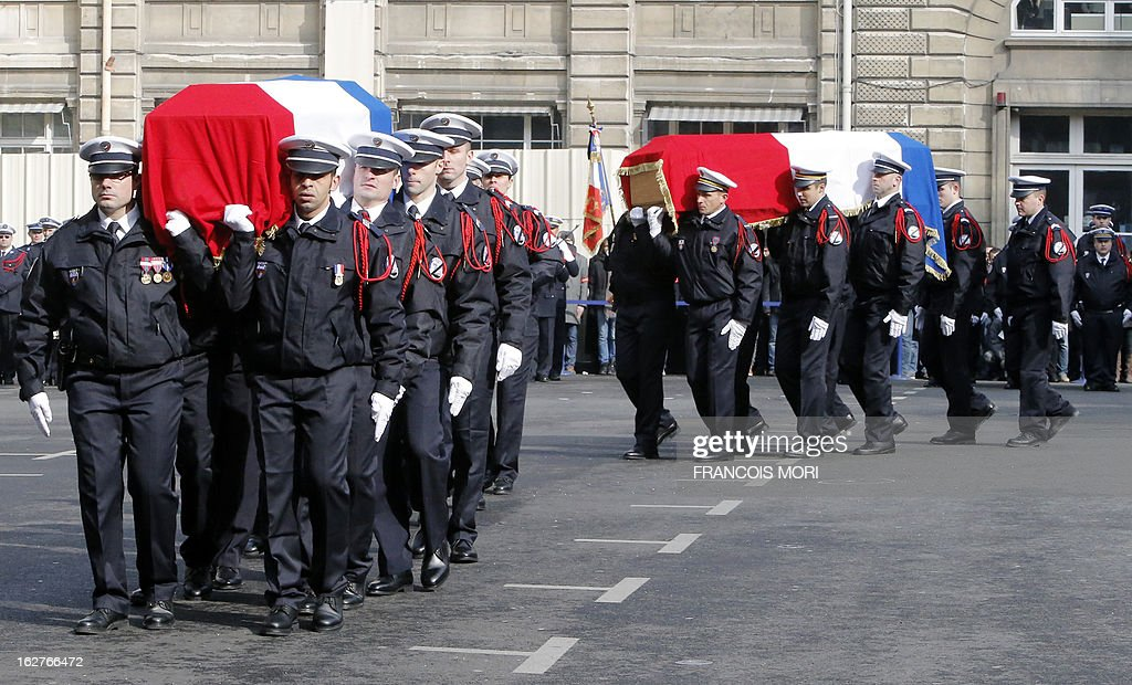Policemen carry the coffins of their two colleagues, killed in a collision in Paris during a high-speed chase, during a ceremony in the yard of the Paris police prefecture, on February 26, 2013 in Paris. An alleged drunk driver killed the two Paris police officers after slamming his black Land Rover into their cruiser during a high-speed chase five days ago, on the ring road around Paris.