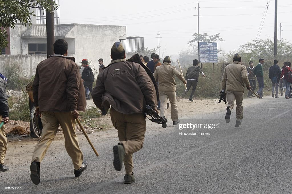 Policemen chasing protestors after protest by students in support of rape victim at Sector 49 on December 27, 2012 in Noida, India. Huge traffic jam was witnessed and agitated mob ransacked some vehicles after which police had to Lathi charge to bring situation back to normal.