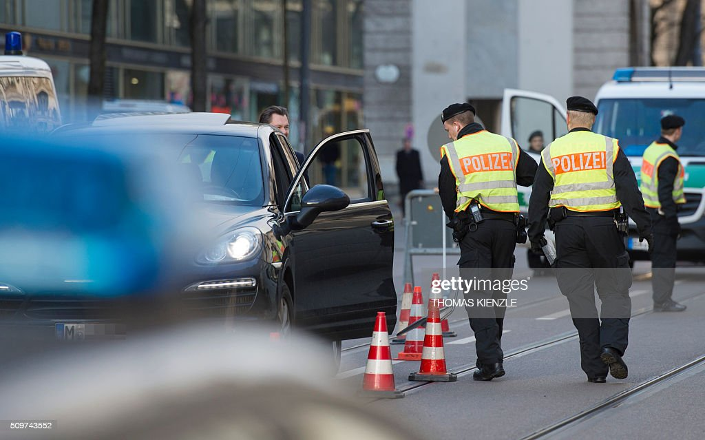 Policemen check a car as security measures are executed in front of the Bayerischer Hof hotel, venue of the 52nd Munich Security Conference (MSC), prior to the start of the conference in Munich, southern Germany, on February 12, 2016. The Munich Security Conference takes place here until February 14, 2016. / AFP / THOMAS KIENZLE