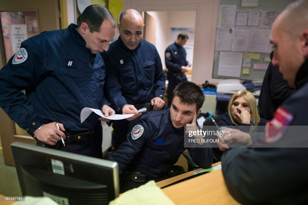 Policemen check a man's identity on a computer in the Gare du Nord (North railway station) police station in Paris on November 29, 2012 .