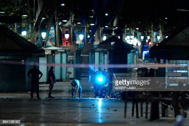 Policemen check the area after towing away the van which ploughed into the crowd killing at least 13 people and injuring around 100 others on the...