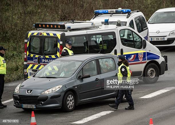 Policemen check the identity of motorists as part of security measures set following terrorist attacks in Paris on November 17 2015 at the...