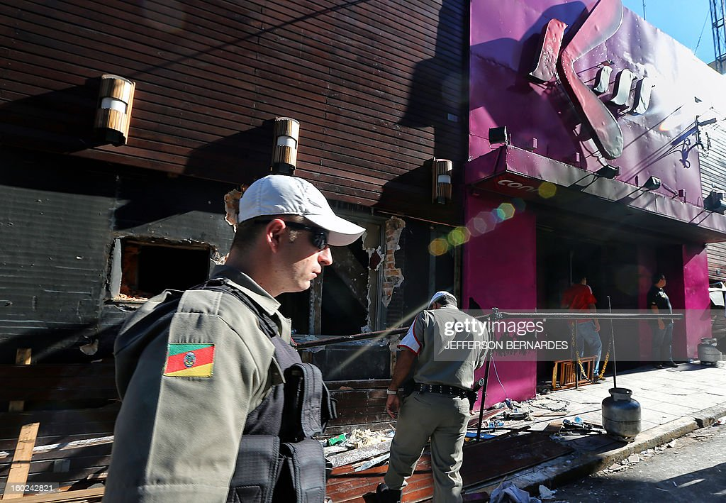 Policemen check the Kiss nightclub where a blaze on the eve killed more than 230 people, on January 28, 2013 in Santa Maria, southern Brazil. Brazilian police arrested four suspects --two of the Kiss club's owners, along with a pair of musicians who starred in the ill-fated pyrotechnic show, in the wake of the nightclub fire that forced sports officials to defend preparations for the World Cup and Olympics. AFP PHOTO / JEFFERSON BERNARDES