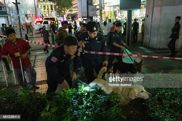 Policemen check with sniffer dogs at the scene of an explosion on August 17 2015 in Bangkok Thailand A large explosion believed to a bomb has hit...