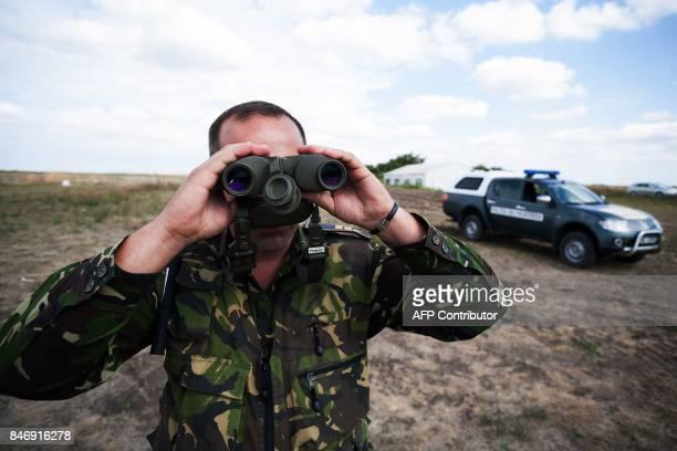 A policemen checks the border area at Triplex Confinium where the borders of Romania Hungary and Serbia meet near Beba Veche western Romania on...