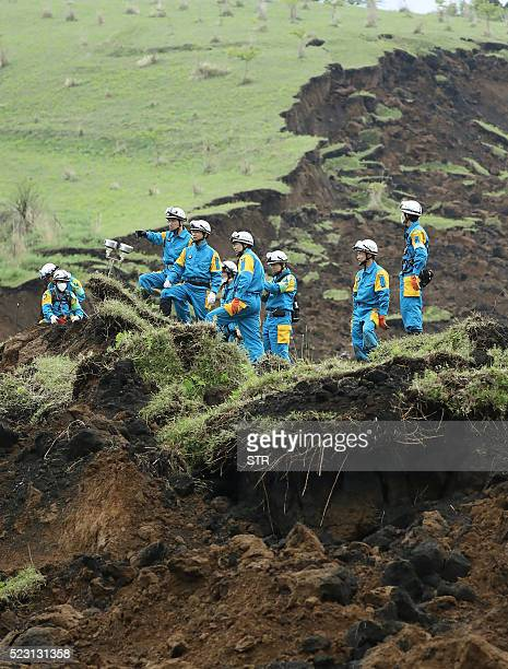 Policemen ckeck a landslide site before searching for missing people in MinamiAso Kumamoto prefecture on April 22 2016 While the death toll from the...