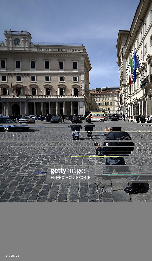 Policemen clear the area where a Carabiniere police officer was shot by an apparently disturbed man, on April 28, 2013 in Rome, outside the palazzo Chigi, the Italian Prime minister offices, while the country's new ministers were being sworn in. Two policemen were wounded, as well as a passerby, in the shooting. The attacker, named by Italian media as businessman Luigi Preiti, 49, was tackled to the ground by by police as witnesses fled the scene. AFP PHOTO / FILIPPO MONTEFORTE