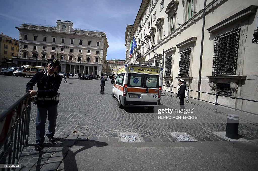 Policemen clear the area where a Carabiniere police officer was shot by an apparently disturbed man, on April 28, 2013 in Rome, outside the palazzo Chigi, the Italian Prime minister offices, while the country's new ministers were being sworn in. Two policemen were wounded, as well as a passerby, in the shooting. The attacker, named by Italian media as businessman Luigi Preiti, 49, was tackled to the ground by by police as witnesses fled the scene.