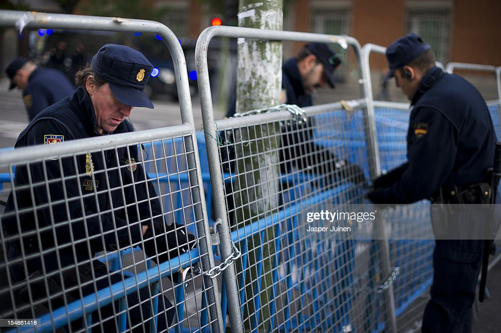 Policemen close barricades in front of the Spanish Parliament prior to the start of a protest against spending cuts and the government of Mariano Rajoy on October 27, 2012 in Madrid, Spain. Demonstrators are protesting near the Spanish Parliament against the government's austerity measures. With the economic crisis tightening it's grip, Spain is in its second recession in three years, Rajoy's governement is presssured more and more to seek aid that can easy their debts.
