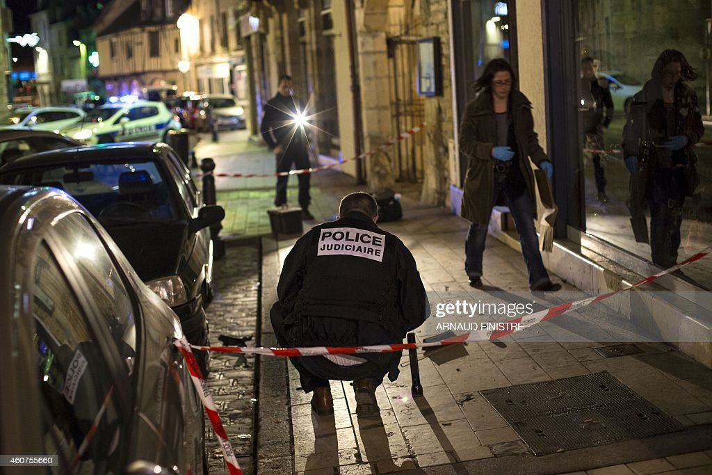Policemen collect evidence on December 21, 2014 in Dijon on the site where a driver shouting 'Allahu Akbar' ('God is great') ploughed into a crowd injuring 11 people, two seriously, a source close to the investigation said. Two of the people injured in the car attack in the city of Dijon were in a serious condition, a police source said, adding that the driver had been arrested.