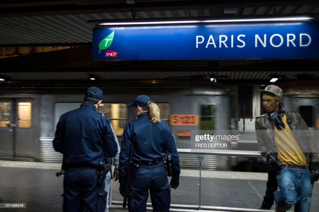 Policemen conduct an indentity check on a man in the Gare du Nord (North railway station) in Paris on November 30, 2012 .