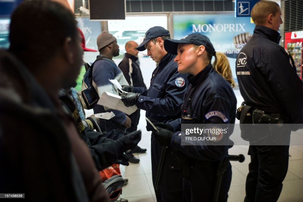 Policemen conduct identity checks on a group of men in the Gare du Nord (North railway station) in Paris on November 30, 2012.